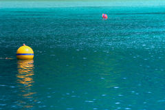 Yellow buoy on turquoise sea Stock Photography