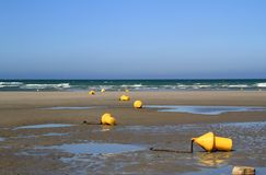 Yellow buoys on the beach at low tide Stock Photo