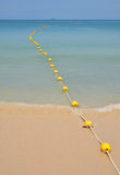 Yellow buoys at sea beach in perspective. Chain of yellow polystyrene sea marker buoys with cable tow at sand beach and in blue sea water with clear sky above stock photo