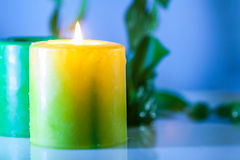 Yellow Burning Candle - Spa concept. Yellow candle light with green leaves and water reflection Stock Photo