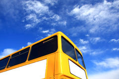Yellow Bus & Blue Sky. A shiny Yellow Bus set against a bright Blue Sky, marbled with white clouds Stock Images