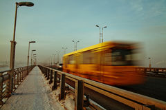 Yellow bus on the bridge. Shooting on road of a winter townscape with cars in movement Stock Photos