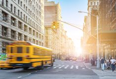 Yellow bus driving fast down Fifth Avenue in Manhattan New York City. With sunlight shining in background royalty free stock photos