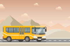 Yellow bus goes on the highway in the desert. Mountains, road and clouds Stock Photo