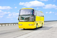 Yellow bus on road. Yellow bus on a sunny road royalty free stock images