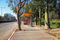 Yellow bus shelter at weekend. Rishon Le Zion, Israel - March 14, 2015: Yellow bus stop Ben Gurion- Begin is deserted at weekend. Red movie poster is placed in Royalty Free Stock Image