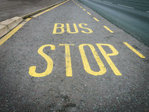 Yellow bus stop sign painted on the road asphalt Stock Image