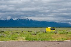 Yellow bus on a valley road stock photography