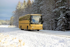 Yellow Bus on Winter Road. Yellow coach bus travels along rural highway in winter landscape with snow. Copy space for your text stock photo