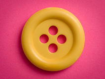 Yellow button. On pink paper Royalty Free Stock Photography