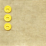Yellow buttons on beige fabric Royalty Free Stock Photo