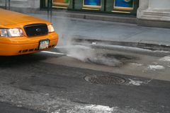 Yellow Cab. Close up of yellow cab with smoking pot hole in Manhattan Royalty Free Stock Images