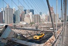Yellow cab on Brooklyn bridge. A shot of a cab driving through Brooklyn bridge Royalty Free Stock Photography
