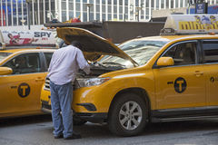 Yellow cab driver looking at engine of his taxi Stock Photo