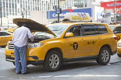 Yellow cab driver looking at engine Royalty Free Stock Image
