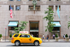 Yellow cab driving past Tiffany and Co, New York. Yellow cab driving past the front facade of Tiffany and Co, New York, a famous breakfast venue and retailer in royalty free stock image