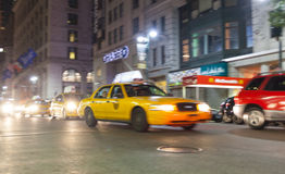 Yellow cab at night in New York City in motion blur. Royalty Free Stock Image