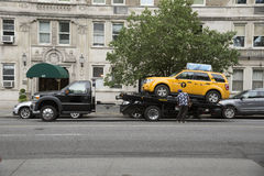 Yellow cab on a tow truck New York USA stock photos