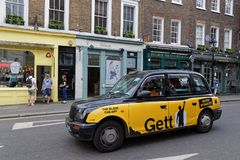 Yellow cab and yellow store. LONDON, GREAT BRITAIN, April 21, 2018 : Hackney carriage or Black Cab in the streets of London. In the United Kingdom, the name Stock Photography