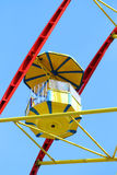 Yellow cabin of colorful Ferris wheel and clear blue sky Royalty Free Stock Photo