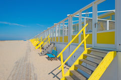 Yellow cabins on a beach in sunlight Royalty Free Stock Photos