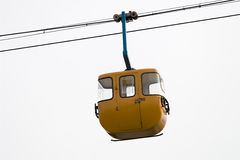 Yellow cable car hanging. Photo of yellow cable car hanging in the sky Royalty Free Stock Photography