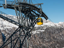 Yellow cable car ski lift going up on the mountain top Royalty Free Stock Photography