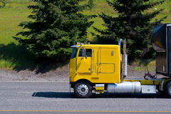 Yellow cabover big rig semi truck old model on road Royalty Free Stock Image