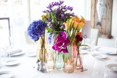 Flowers in vase on table. Yellow callas, violets, roses and pansies stand in vase on table with white tablecloth next to plates and glasses Stock Photos