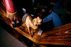 Yellow camel figure with a black cape stands on a wooden shelf stock photography