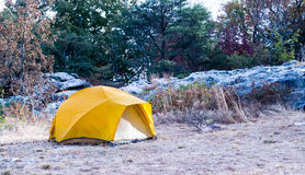 Yellow camping tent, mountains, trees. Solitary camping on bluff near mountain cliff and trees. Yellow tent provides shelter for camping experience Royalty Free Stock Photos
