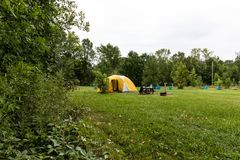 Yellow Camping tent near the forest on grassland. Yellow Camping tent on grassland near the wood green forest country environment fresh equipment active camp royalty free stock photo
