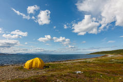 Yellow camping tent on a shore Royalty Free Stock Photos