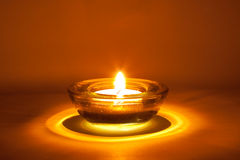 Yellow candle. Candle illuminating a dark room Stock Image