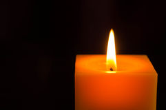 Yellow candle on a black background Stock Photos
