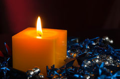 Yellow candle among a blue and Christmas decor Royalty Free Stock Image