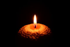 Yellow candle burning on a black background Stock Image