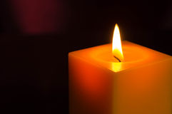 The yellow candle burning in the dark Stock Photo
