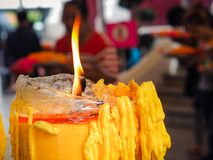 Yellow candle burning in old church. Royalty Free Stock Image