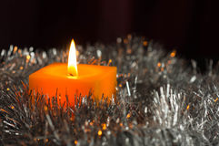 The yellow candle burns among a silvery decor Stock Photos