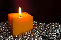 Yellow candle with a decor from silver balls. Close up stock images