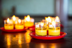 Yellow candle glass. Yellow candle in glass catch fire and red plate on wooden table Royalty Free Stock Photo