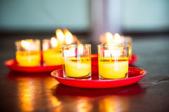 Yellow candle glass. Yellow candle in glass catch fire and red plate on wooden table Royalty Free Stock Images