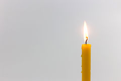 Yellow candle. Candle light  for spirituality ceremony against grey background Stock Image