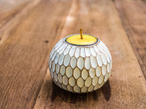Yellow candle in patterned holder Stock Image