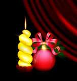 Yellow candle and red ball. Black background, dark crimson drape and the large red ball with branch of tree and bow, the big yellow burning candle Royalty Free Stock Images