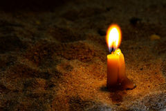 Yellow candle on sand at night. Royalty Free Stock Photography
