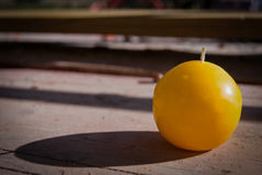 Yellow candle with shadow. Candle put outside on wood board Royalty Free Stock Photography