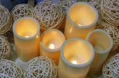Yellow candles on the background of rattan balls royalty free stock image