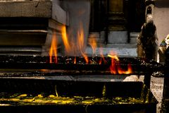 Yellow candles burning on black metal holder with orange flame and yellow candle tears underneath in a Buddhist temple. stock photos